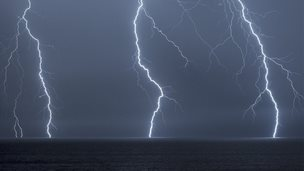 Three bolts of lightning hitting the sea