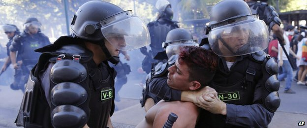 A protestor is restrained by police in Rio on 13 July