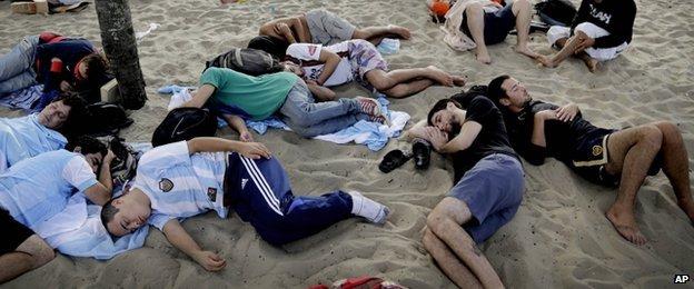 Fans sleep on Copacabana beach, 15 June 2014