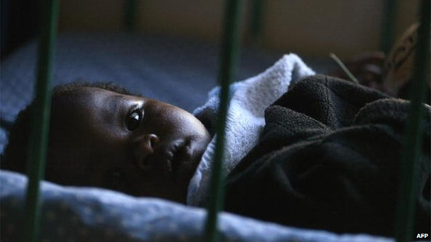 A young HIV-positive orphan lies in his cot at the Nyumbani Children's Home in Nairobi, Kenya - 2005