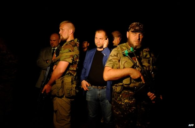 Alexander Borodai surrounded by bodyguards at the crash site in east Ukraine, 17 July
