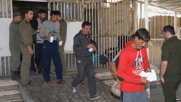 Syrian prisoners leaving a jail in Damascus on 11 June