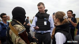Organisation for Security and Co-operation in Europe (OSCE) monitors speak with a pro-Russian separatist (second left) at the site of Thursday's Malaysia Airlines Boeing 777 plane crash near the settlement of Grabovo in the Donetsk region, Ukraine, 18 July 2014