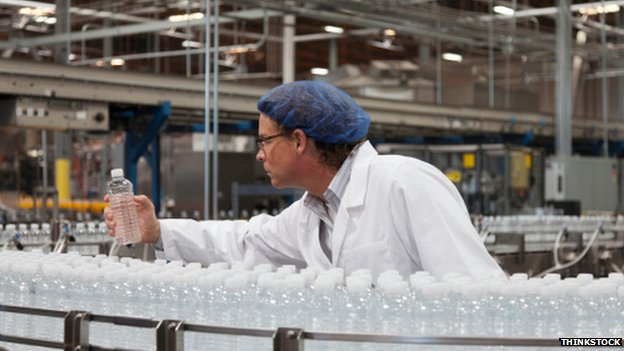 Factory worker examines water bottle