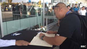 Passengers signing a book of condolences set up at Schiphol Airport