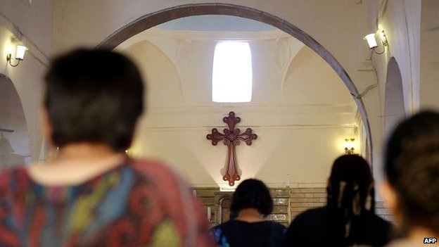 Iraqi Christians pray at a church outside the city of Mosul after fleeing violence - 1 July 2014