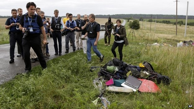 OSCE observers inspect the site of the crash in eastern Ukraine under the watchful eye of armed rebels - 18 July 2014