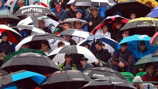 Golf fans sheltering under umbrellas
