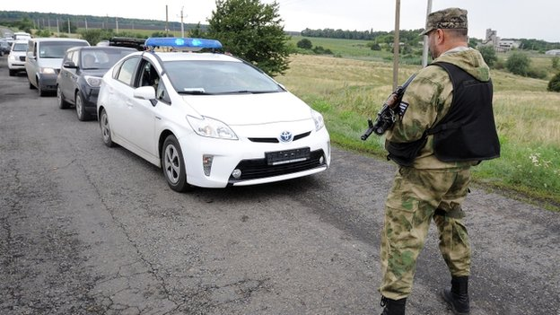 An armed man stops traffic near the site of the crash of a Malaysia Airlines plane in rebel-held east Ukraine, on 19 July 2014