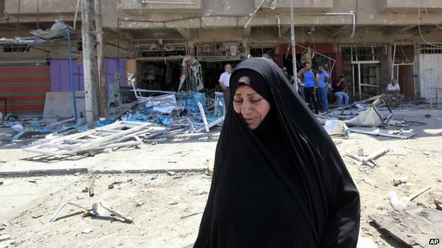 Civilians inspect the site of a bomb attack in the Jihad district in Baghdad, 19 July 2014