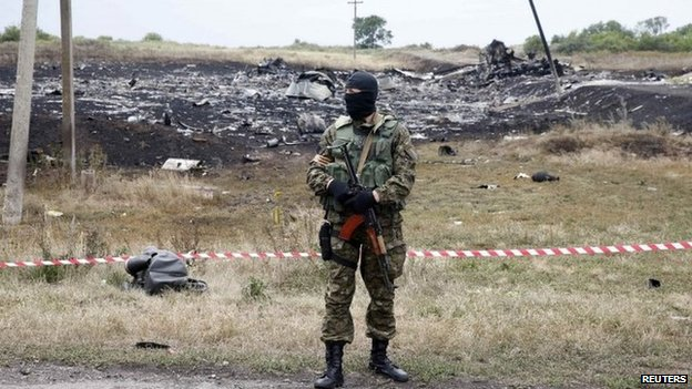 A pro-Russian separatist stands at the crash site of Malaysia Airlines Flight MH17, near Grabovo in eastern Ukraine, 19 July 2014