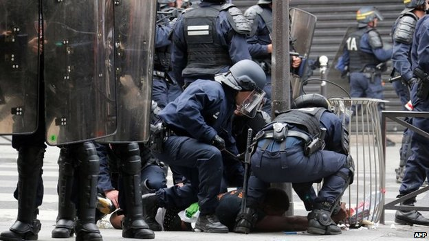 French riot police officers bring a man down on the ground near the aerial metro station of Barbes-Rochechouart, in Paris, 19 July 2014