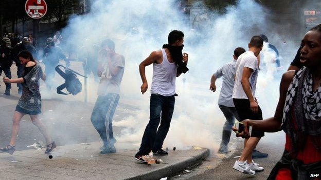 Protesters run to avoid tear gas near the aerial metro station of Barbes-Rochechouart, in Paris, 19 July 2014