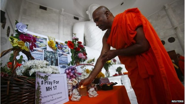 A monk performs a prayer during a special vigil for victims of the downed Malaysia Airlines Flight MH17, inside a Buddhist temple in Kuala Lumpur July 20, 2014