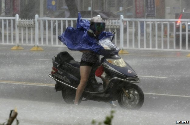 A woman rides an electric bicycle through the typhoon in Zhanjiang, in China's Guangdong province, 18 July