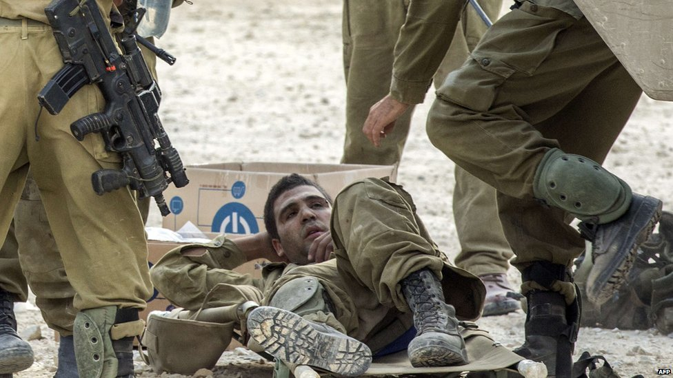 Israeli soldiers evacuate their wounded comrades at an army deployment area near Israel's border with the Gaza Strip, on 20 July 2014.