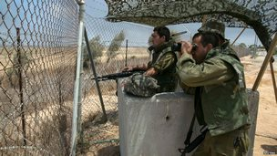 An Israeli soldier looks through binoculars near the border with Gaza July 20, 2014.