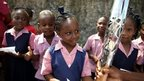 Students from Charles F Broome Primary School reach out to touch the Queen's Baton in Barbados.