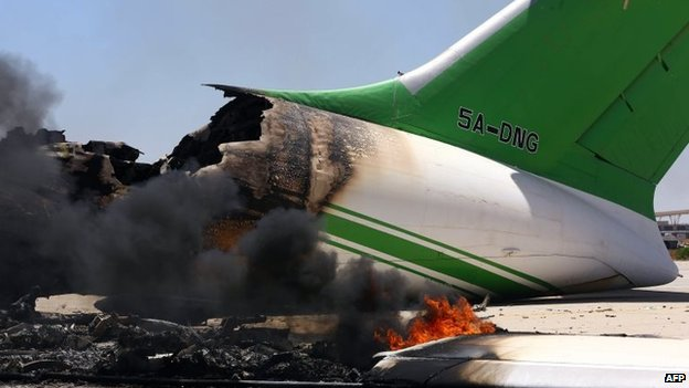 Flames and smoke billowing from an airplane at the Tripoli international airport in the Libyan capital, 16 July 2014