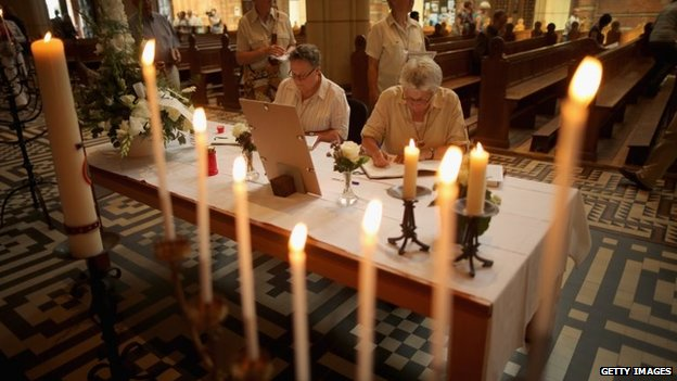 People sign a book of condolence during a special mass in Saint Vitus church in memory of the victims of Malaysia Airlines flight MH17, in Hilversum, Netherlands, 20 July 2014
