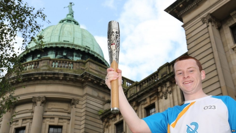 "Batonbearer 023 Nathan Arbuckle carrying the Glasgow 2014 Queen""s Baton at the Mitchell Library in Glasgow."