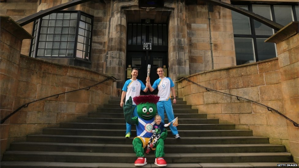 "Batonbearer 025 William Mitchell and Batonbearer 026 Michael Aldridge, with Clyde the Glasgow 2014 mascot, hold the Glasgow 2014 Queen""s Baton at the Glasgow School of Art"