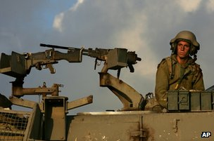 An Israeli gunner sits in a mobile artillery piece as it waits to fire into southern Lebanon from a position near Kiryat Shmona, northern Israel, 14 July 2006