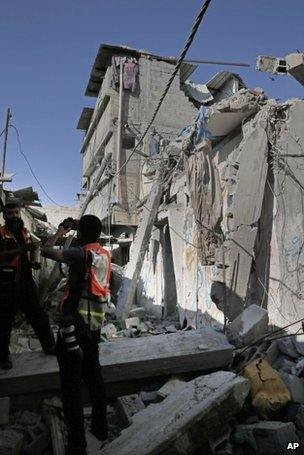 Palestinian rescue workers inspect a bomb-damaged building in Gaza City, 20 July