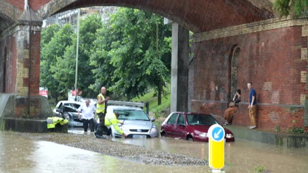 Cars stuck in flood water under a bridge