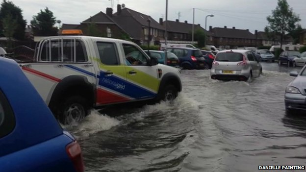 Cars moving through flooded road in Canvey Island