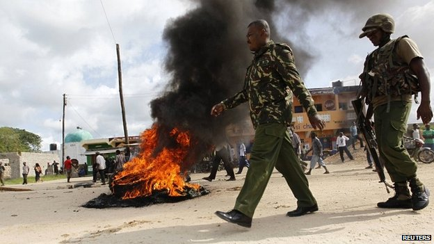 Kenyan police officers walk past a fire on a street in Mpeketoni after an attack by gunmen - 17 June 2014