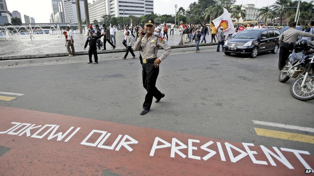 A police officer walks past a message taped on the road by supporters of presidential candidate Joko Widodo, during a rally in Jakarta, Indonesia on Thursday, 10 July, 2014