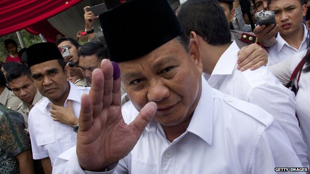Indonesian presidential candidate Prabowo Subianto waves with an ink-stained finger after voting in his local polling station on 9 July, 2014 in Bojong Koneng, Indonesia