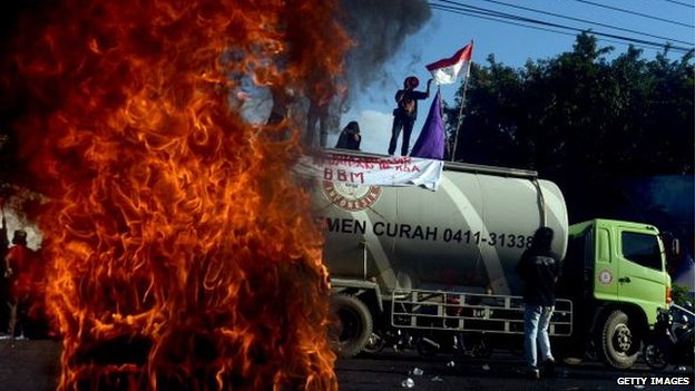 Demonstrators burn tyres near a cement truck during a May Day rally outside the local parliament of Makassar city in Sulawesi island on 17 June, 2013