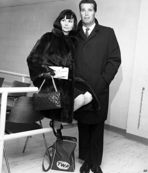 Actor James Garner, right, and his wife Lois are shown in the Trans World Flight Center prior to boarding a TWA Jetliner enroute to London in this Feb. 21, 1964