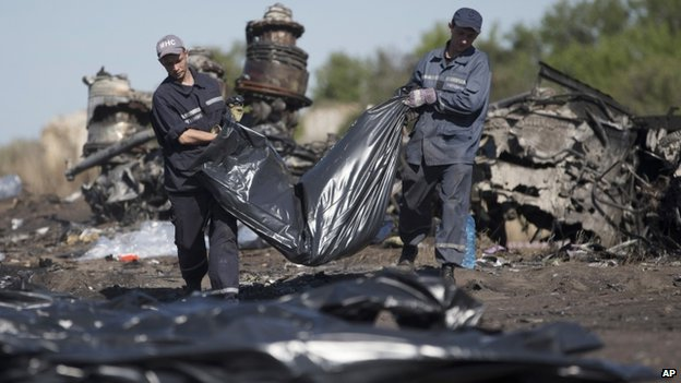 Ukrainian Emergency workers carry a victim's body in a bag at the crash site of Malaysia Airlines. Photo: 21 July 2014