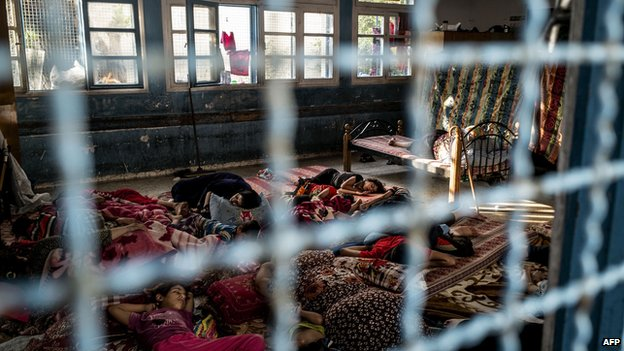Displaced Palestinians rest at a UN school in Gaza (21 July 2014)