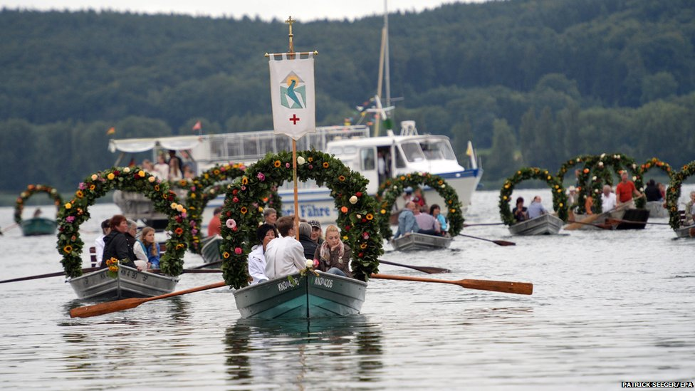 Boats decorated with flower wreaths sail during the Water Procession of Moos on Lake Constance into the harbour of Radolfzell, Germany