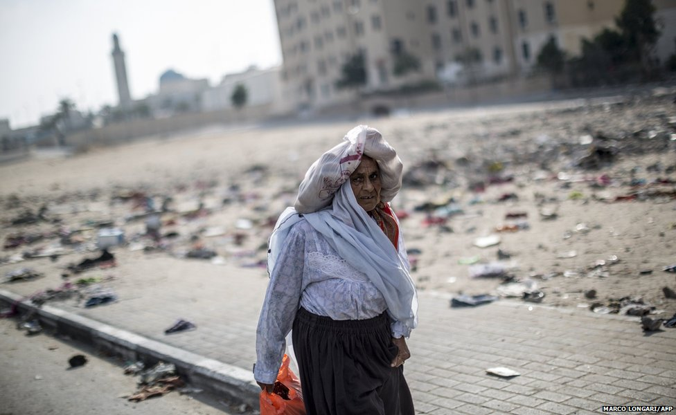 A displaced woman from the northern Beit Hanun district in the Gaza Strip walks towards a UN school in Beit Lahia