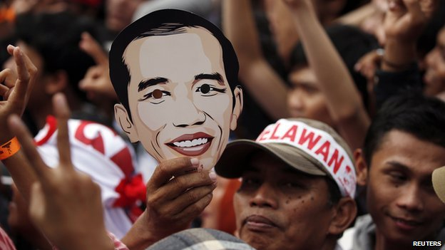 A supporter of Indonesian presidential candidate Joko Widodo holds a mask during a rally at Gelora Bung Karno stadium in Jakarta on 5 July, 2014
