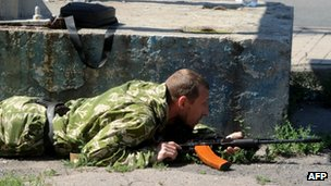 An armed pro-Russia separatist lies on the ground near the train station in Donetsk as intense shelling rocks the area