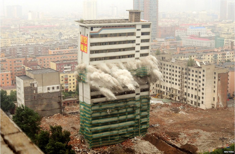 The former Heilongjiang TV station headquarters collapses as it is demolished by explosives to make way for the city's new administrative service centre in Harbin, Heilongjiang province, China