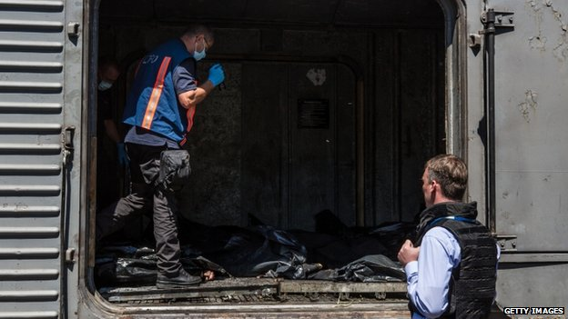 Dutch investigators and OSCE monitors examine the bodies in Torez. Photo: 21 July 2014