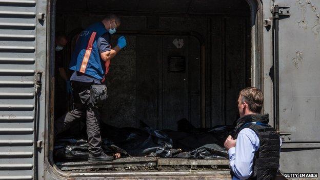 Dutch investigators and OSCE monitors examine the bodies in Torez. Photo: 21 July 2014
