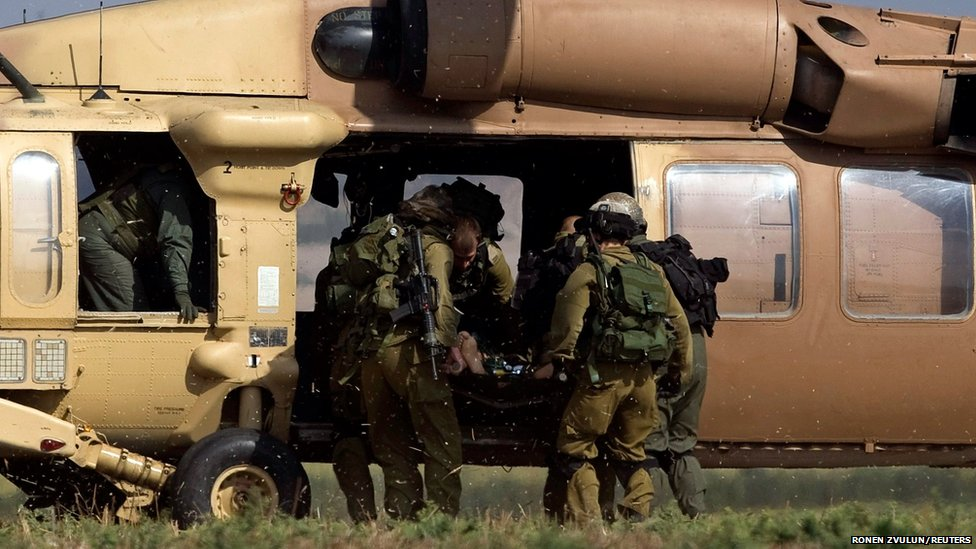 A wounded Israeli soldier is carried on a stretcher into an awaiting helicopter for evacuation outside Gaza