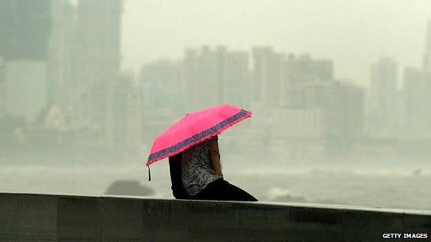 A couple huddle together under an umbrella in Mumbai