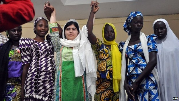 Pakistani education activist Malala Yousafzai raises her arms as she poses with five escaped Chibok school girls (LtoR) Rebecca Ishaku, Kanna Bitrus, Hauwa John, Hauwa Musa and Hawa Alhl'ama during a press conference in Abuja, Nigeria, on 14 July 2014