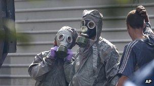 Two people wearing protective suits and gas masks
