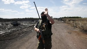 An armed pro-Russian separatist at the crash site of MH17 near the village of Hrabove (Grabovo) in the  Donetsk region