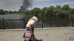 A Ukrainian elderly woman hurries to cross a bridge across a river in the city of Donetsk, eastern Ukraine